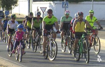 Grupo personas montando en bicicleta por la mitad de la carretera, debido a Marcha Cicloturista Nocturna